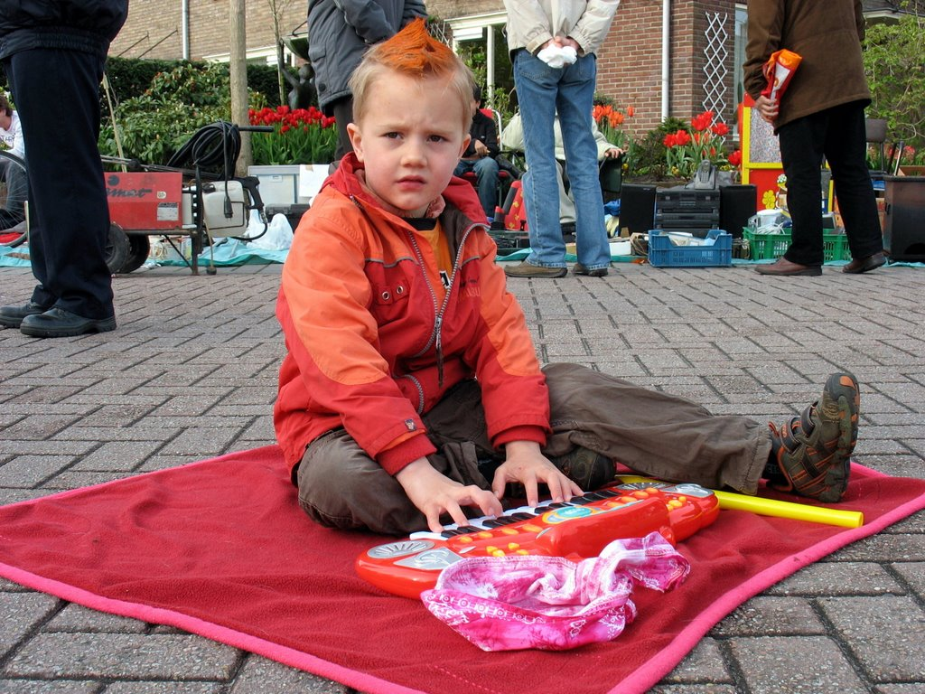 Little boy on Queensday, he is playing on his organ