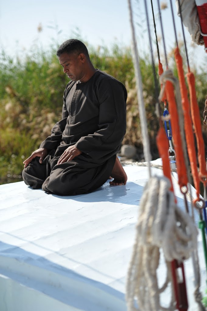 Our friendly boatman Mahmoud praying on his boat in front of Jolie Ville